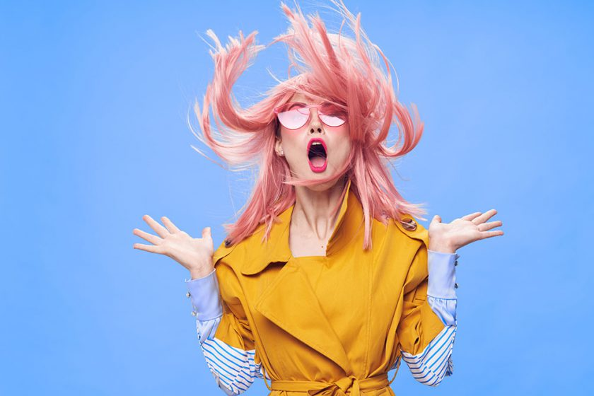 Woman in a pink wig, clothes on a pink background with food